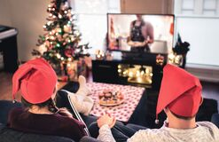 Free Couple Watching Tv On Christmas. Happy Family Holiday At Home. Man And Woman On Couch Relaxing With Tree, Decorations, Lights. Stock Photo - 203480150