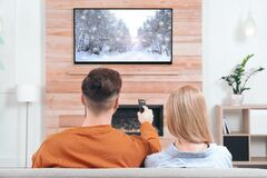 Free Couple Watching TV On Sofa In Room With Decorative Fireplace Royalty Free Stock Photography - 182964407