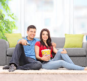 Couple watching TV seated on the floor at home Royalty Free Stock Photos