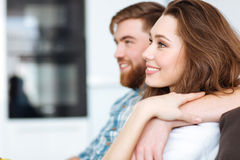 Couple watching TV on the sofa. Portrait of a happy couple watching TV on the sofa at home Royalty Free Stock Photography