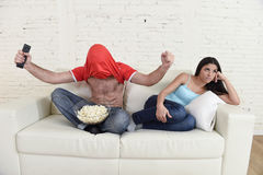 Couple watching tv sport football with man excited celebrating crazy happy goal and woman bored. Young couple watching tv sport football game with men excited Stock Photo