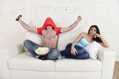 Couple watching tv sport football with man excited celebrating crazy happy goal and woman bored. Young couple watching tv sport football game with men excited Royalty Free Stock Images
