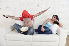 Couple watching tv sport football with man excited celebrating crazy happy goal and woman bored Royalty Free Stock Photo