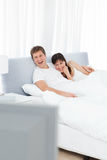 Couple watching tv in their bed Royalty Free Stock Photography