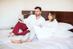 Couple watching TV on their bed Royalty Free Stock Photography