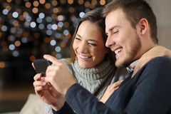 Couple watching videos in a phone in the night. Sitting on a couch in the living room at home royalty free stock image