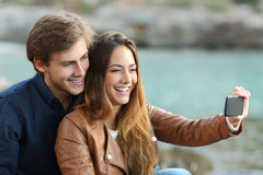 Couple watching videos in a smart phone Stock Photo