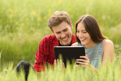 Couple watching videos in a tablet in a field Stock Images