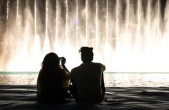 A couple watching the water and light show of Dubai Mall fountai. Dubai, UAE - May 25, 2018: A couple watching the light and water show of Dubai Mall fountains Stock Image