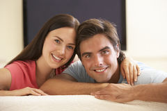 Couple Watching Widescreen TV At Home Stock Photo