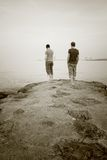 Couple water. Couple at the seaside. two male looking out over the sea or ocean. Water on day with haze, mist or fog Royalty Free Stock Photo