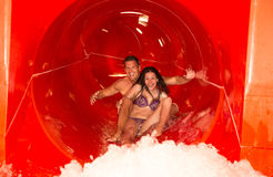 Couple in water slide at public swimming pool Stock Photo