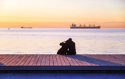 Couple on the waterfront in golden hour. Couple in love on the waterfront makes a heart with their hands in golden hour. Photo taken in Thessaloniki, Europe stock photos
