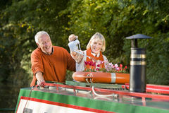 Couple watering potted flowers on boat Stock Images