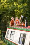Couple watering potted flowers on boat in canal Royalty Free Stock Photography