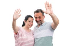 Couple waving as greeting gesture. Man and women couple waving as greeting gesture with friendly expression isolated on white studio background royalty free stock photography