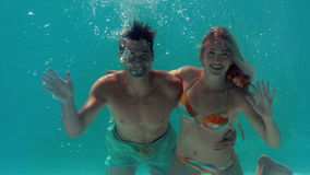 Couple waving at camera in the swimming pool. In slow motion stock video footage