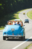 Couple Waving Hands. Sitting in blue cabriolet Stock Photo