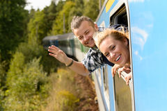 Couple waving with heads out train window Royalty Free Stock Image