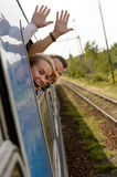 Couple waving with heads out train window Royalty Free Stock Photo