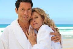 Couple wearing a bathrobe. Mid aged couple wearing a bathrobe near the sea royalty free stock photography