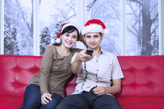 Couple wearing christmas hat watching tv Royalty Free Stock Images