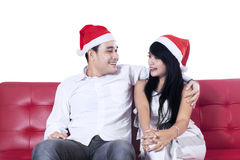 Couple wearing christmas hats on couch Stock Photo