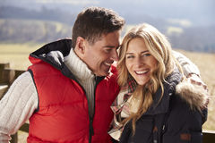 Couple wearing coats embracing in the countryside Stock Photo