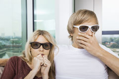 Couple wearing 3D glasses and watching TV with concentration at home Royalty Free Stock Photo