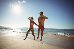 Couple wearing diving mask jumping on beach Stock Photos