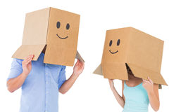Couple wearing emoticon face boxes on their heads Stock Image