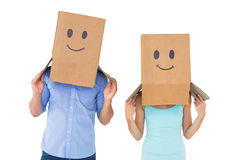 Couple wearing emoticon face boxes on their heads Stock Photo
