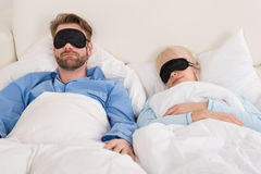 Couple Wearing Eyemask While Sleeping On Bed Royalty Free Stock Images