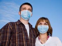 Couple wearing flu masks Stock Images