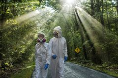 Couple wearing hazmat suits. On country road Royalty Free Stock Photo