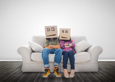 Couple wearing humorous boxes on their head. On a couch Royalty Free Stock Photos