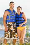 Couple wearing life jackets at beach Royalty Free Stock Images