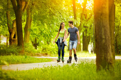 Couple wearing in line skates in park Stock Photography