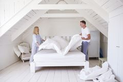 Free Couple Wearing Pajamas Making Bed In Morning Royalty Free Stock Images - 104868179