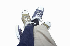 Couple wearing plimsoles, legs entwined, cut out Stock Image