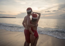 Couple wearing santa hat at the beach Stock Photography