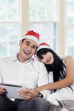 Couple wearing santa hat and smiling on camera Royalty Free Stock Image