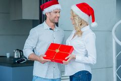 Couple Wearing Santa Hats Exchanging Gift Stock Photos