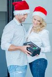Couple Wearing Santa Hats Exchanging Gift Royalty Free Stock Photography
