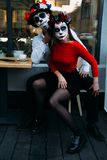 A couple, wearing skull make-up for. All souls day. Boy and girl sugar skull makeup.painted for halloween sit in a cafe. dead in t stock photo