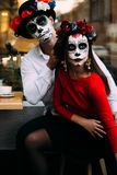 A couple, wearing skull make-up for. All souls day. Boy and girl sugar skull makeup.painted for halloween sit in a cafe. dead in t stock photos