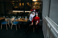 A couple, wearing skull make-up for. All souls day. Boy and girl sugar skull makeup.painted for halloween sit in a cafe. dead in t stock images