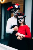 A couple, wearing skull make-up for. All souls day. Boy and girl sugar skull makeup.painted for halloween standing on the street. royalty free stock photo