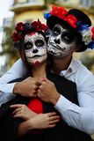 A couple, wearing skull make-up for. All souls day. Boy and girl sugar skull makeup.painted for halloween standing on the street. stock photos