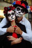 A couple, wearing skull make-up for. All souls day. Boy and girl sugar skull makeup.painted for halloween standing on the street. stock images